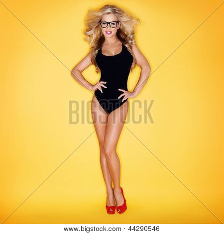 Blonde Woman In Swimsuit Wearing Eyeglasses On Yellow Background