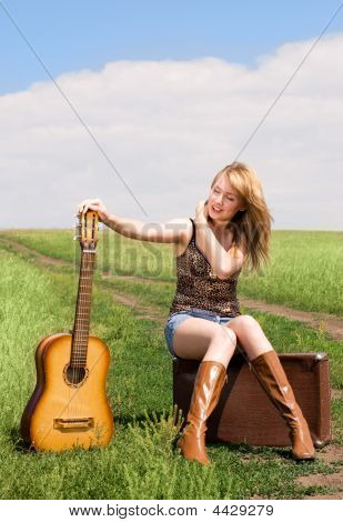Girl With A Guitar And Suitcase Outdoor
