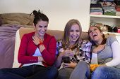 pic of couch potato  - Laughing young girls watching TV together sitting on couch - JPG