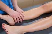 lymphatic drainage massage therapist hands on woman leg ankle