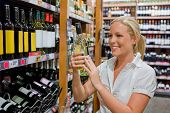 stock photo of local shop  - a woman buys wine in a supermarket - JPG