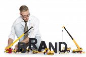 Build up a brand concept: Focused businessman building the word brand along with construction machin
