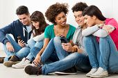 pic of sms  - Group Of Happy Young Friends Looking At Cell Phone - JPG