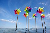 stock photo of windmills  - Toy windmill concept of green energy wind farm at sea - JPG