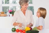 Grandmother cutting vegetables looking at her grandson in kitchen