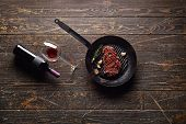 pic of veal  - Marbled beef steak in a grill pan with a bottle of wine and wine glass on old wood background - JPG