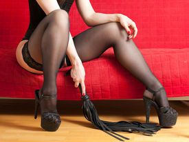 stock photo of sado-masochism  - The woman in black corset and stockings sitting on a red couch and holding a whip - JPG