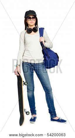 Full-length portrait of teenager with skateboard wearing sunglasses, peaked cap, earphones and rucksack, isolated on white. Concept of young generation