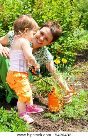 Helfende Mutter im Garten