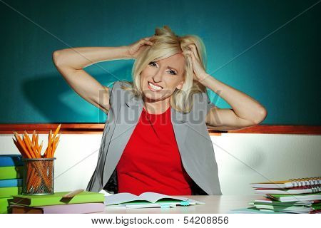Irate teacher sitting at table on blackboard background