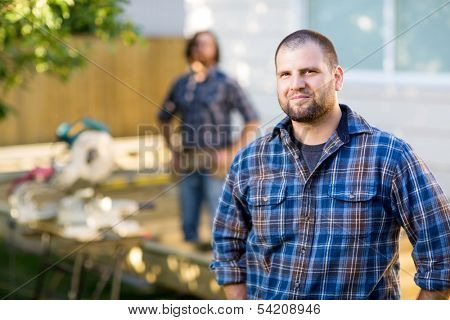Portrait of mid adult manual worker in casual shirt standing with coworker in background at construction site