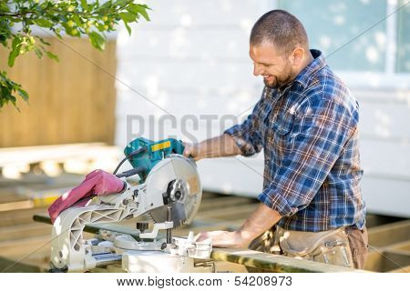 Happy mid adult carpenter cutting wood using table saw at construction site