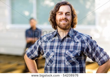 Portrait of mid adult manual worker smiling while coworker standing in background at construction site