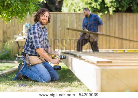 Portrait of confident manual worker drilling wood with coworker working in background at construction site