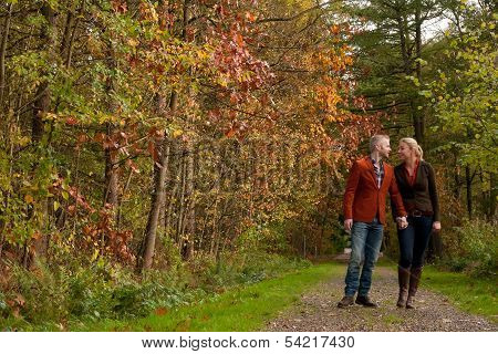 Happy Couple Is Taking A Walk In The Forest