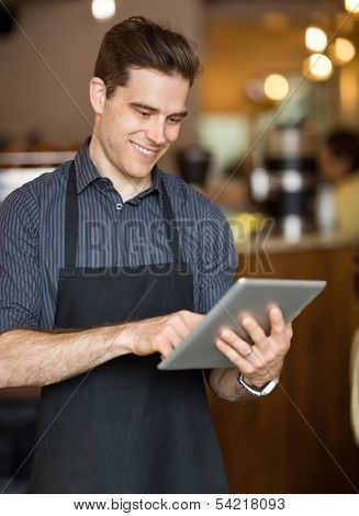 Smiling male owner surfing internet on digital tablet in cafeteria