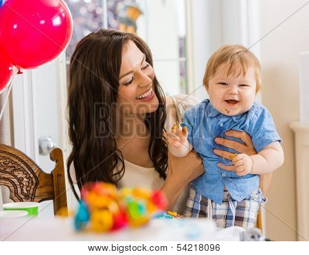 Happy mother holding baby boy at birthday party