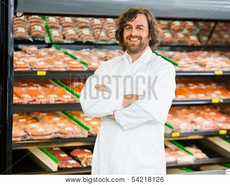Portrait of confident salesman standing arms crossed in butcher's shop