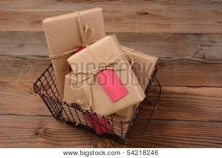 High angle shot of Christmas Presents wrapped in eco friendly craft paper ina a wire shopping basket. Horizontal format on a rustic wooden table.