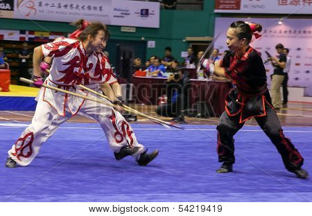 KUALA LUMPUR - NOV 05: Members of the Hong Kong dalian team performs a fight scene in the Women's Dual Event at the 12th World Wushu Championship on November 05, 2013 in Kuala Lumpur, Malaysia.