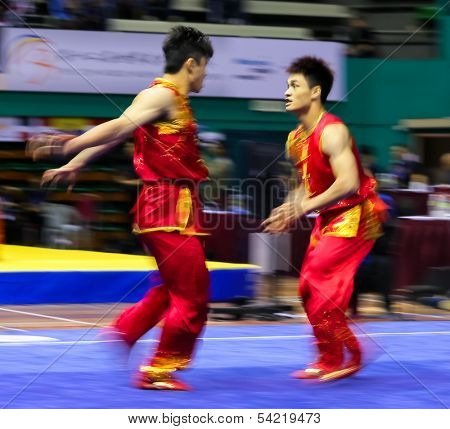 KUALA LUMPUR - NOV 05: Members of Macau's dalian team performs a fight scene in the Men's Dual Event at the 12th World Wushu Championship on November 05, 2013 in Kuala Lumpur, Malaysia.