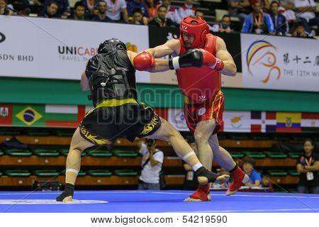 KUALA LUMPUR - NOV 05: Russia's Salikhov Muslim (red) punches Iran's Amir Fazli in the Sanda boxing event, 12th World Wushu Championship on November 05, 2013 in Kuala Lumpur, Malaysia.