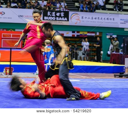 KUALA LUMPUR - NOV 05: Members of Malaysia's dalian team performs a fight scene in the Men's Dual Event at the 12th World Wushu Championship on November 05, 2013 in Kuala Lumpur, Malaysia.