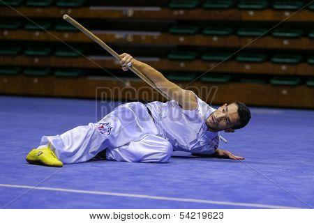 KUALA LUMPUR - NOV 03: Algeria's Amine Nedjani performs with a staff in the Men's 'Nangun' Event at the 12th World Wushu Championship on November 03, 2013 in Kuala Lumpur, Malaysia.