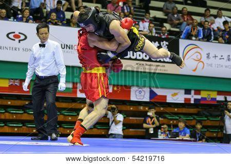 KUALA LUMPUR - NOV 05: Russia's Salikhov Muslim (red) throws Iran's Amir Fazli in the Sanda boxing event, 12th World Wushu Championship on November 05, 2013 in Kuala Lumpur, Malaysia.