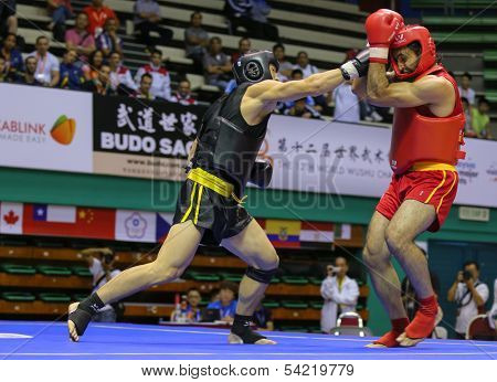 KUALA LUMPUR - NOV 05: China's Bian Qingge (black) trades blows with Egypt's Hisham Amin in the Sanda boxing event, 12th World Wushu Championship on November 05, 2013 in Kuala Lumpur, Malaysia.