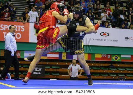 KUALA LUMPUR - NOV 05: Russia's Bektermirov Arslan (black) punches Iran's Hamidreza Gholipour in the Sanda boxing event, 12th World Wushu Championship on November 05, 2013 in Kuala Lumpur, Malaysia.