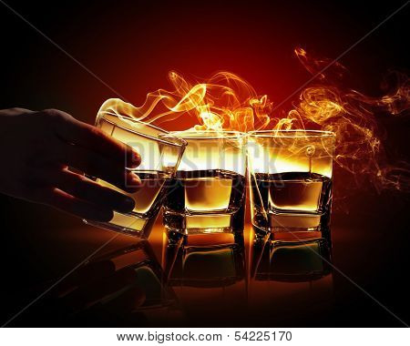 Hand holding one of three glasses of yellow absinth with fume going out