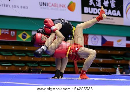 KUALA LUMPUR - NOV 03: Malaysia's Tan Jia Guan (red) fights Sweden's Johan Lindqvist in the Men's 'Sanda' event of the 12th World Wushu Championship on November 03, 2013 in Kuala Lumpur, Malaysia.
