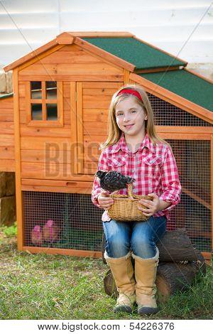breeder hens kid girl rancher blond farmer playing with chicks in chicken hencoop