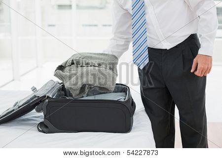 Mid section of a businessman unpacking luggage at a hotel bedroom