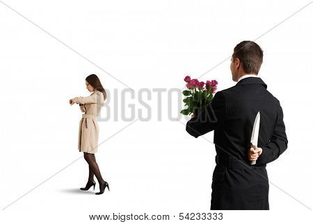crafty man holding knife and looking at young beautiful woman