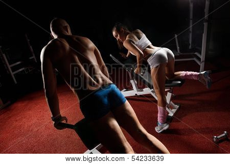 Young bodybuilder training his muscular back and  woman with dumbbells in sport center