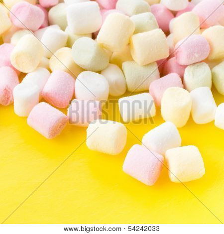A Pile Of Small Colored Puffy Marshmallows  On Bright Yellow  Background Close Up, Top View