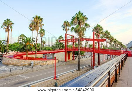 BARCELONA, SPAIN - SEPTEMBER 6: Bridge for pedestrians on Passeig de Colom,   a wide avenue lined with palm trees, Barcelona, Spain on September 6, 2013