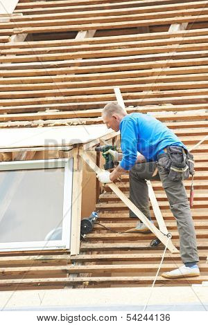 worker on roof at works with flex tile material demounting roofing