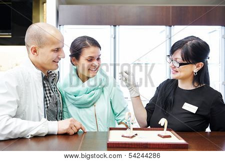 Sales assistant in jewelry shop demonstrating earring to young couple customers during gift selecting