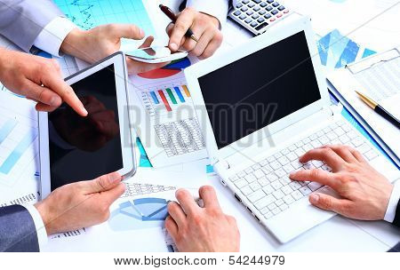 Business work-group analyzing financial data in office