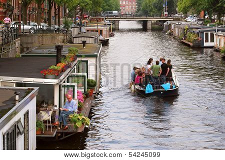AMSTERDAM - JULY 15: Boat with tourists passing by houseboats on city canal. Houseboats are high demand very popular and common form of housing in Amsterdam, Netherlands on July 15, 2007.