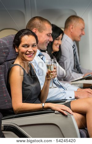Young businesswoman enjoy flight glass champagne airplane cabin travel passenger