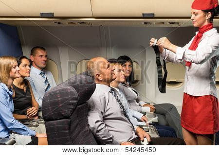 Flight attendant safety demo fastening seat belt passenger airplane cabin