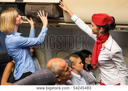Friendly flight attendant helping passenger to put luggage cabin compartment