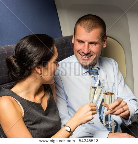 Flight cabin business partners toasting champagne airplane travel passengers
