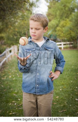 Handsome Young Boy Tossing Up His Baseball in the Park.