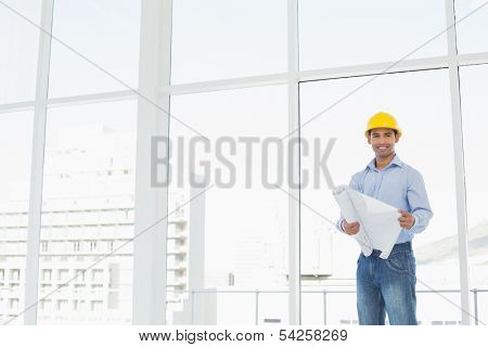 Portrait of a young architect in yellow hard hat with blueprint in a bright office