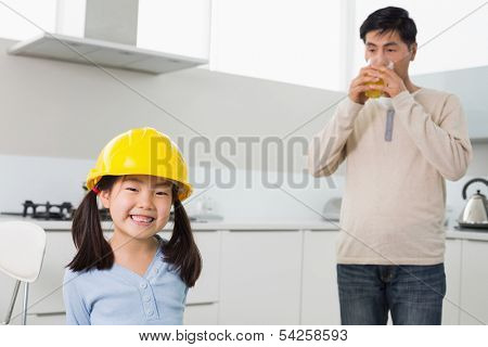 Portrait of a cute girl in yellow hard hat with father drinking orange juice in the kitchen at home